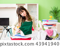 Young woman ironing clothing at home 43941940