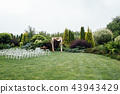 White wedding chairs decorated with fresh flowers on a green grass. 43943429