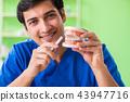 Man dentist working on new teeth implant  43947716