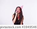 Halloween and carnival concept - young woman with blood on face celebrate holidays with whistle 43949546