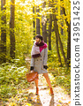 Autumn, nature, people concept - beautiful young woman in a grey coat and a beret standing in the 43951425