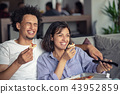 Young Couple with pizza and TV remote 43952859