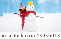 Little boy having fun with snowman in snowy park 43956013