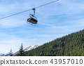 Ski lift against blue sky over wooded Alps 43957010