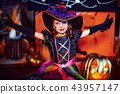 Happy Halloween. A little beautiful girl in a witch costume celebrates with pumpkins 43957147