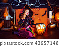 Happy Halloween. A little beautiful girl in a witch costume celebrates with pumpkins 43957148