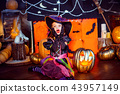 Happy Halloween. A little beautiful girl in a witch costume celebrates with pumpkins 43957149