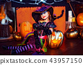 Happy Halloween. A little beautiful girl in a witch costume celebrates with pumpkins 43957150