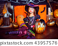 Happy Halloween. A little beautiful girl in a witch costume celebrates with pumpkins 43957576