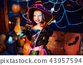 Happy Halloween. A little beautiful girl in a witch costume celebrates with pumpkins 43957594