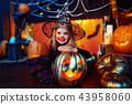 Happy Halloween. A little beautiful girl in a witch costume celebrates with pumpkins 43958060