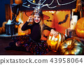 Happy Halloween. A little beautiful girl in a witch costume celebrates with pumpkins 43958064