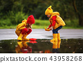 happy children girl and boy with paper boat in  puddle in autumn 43958268