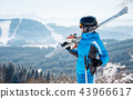 Young female skier with skiing equipment enjoying at winter ski resort in beautiful sunny day 43966617