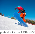 Snowboarder jumping in the air while riding on the slope at winter ski resort in the mountains 43966622