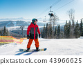 Man standing on his snowboard on a ski slope at winter resort 43966625