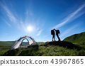 Kiss lovers in mountains at sunlight with an incredible landscape of green hills under blue sky 43967865