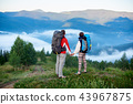 Rear view man and woman with backpacks holding hands on top of hill with view of mountains 43967875
