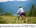 Young happy woman cycling on mountain bike at summer day 43967881