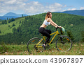 Young happy woman riding bicycle in the mountains at summer day 43967897
