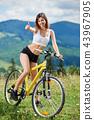 Young happy woman cycling on mountain bike at summer day 43967905