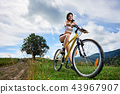 Young happy woman riding bicycle in the mountains at summer day 43967907