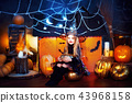Happy Halloween. A little beautiful girl in a witch costume celebrates with pumpkins 43968158