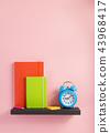 notepad and alarm clock on shelf at wall  43968417