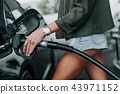 Girl hand keeping the petrol pump nozzle 43971152