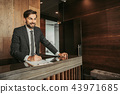 Outgoing male employee making notes on clipboard 43971685