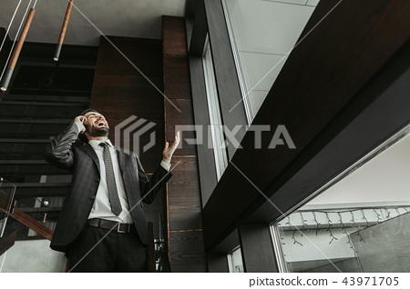 Happy bearded businessman talking on mobile indoor 43971705