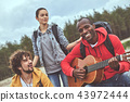 Friends playing the guitar outdoor during their vacation trip 43972444
