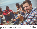 Happy man sitting near his friends at the seaside 43972467