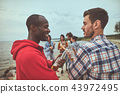 Two friends talking during party on the beach 43972495