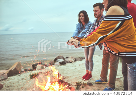Friends spending time together at the sea shore 43972514