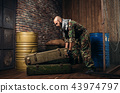 Terrorist in uniform loads boxes of ammunition 43974797