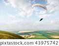 A white-orange paraglider flies over the mountainous terrain 43975742