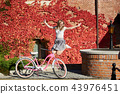 Attractive blond girl at pink lady bicycle on sunny day on wall overgrown with red ivy background. 43976451