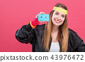 Woman in 1980's fashion holding a cassette tape 43976472