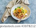 Pasta carbonara with egg yolk in a white plate. 43978212