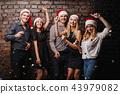 Company of friends in Santa caps dancing 43979082