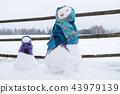 Two cute snowmen wrapped in scarves on field. 43979139