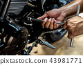 People are repairing a motorcycle. 43981771