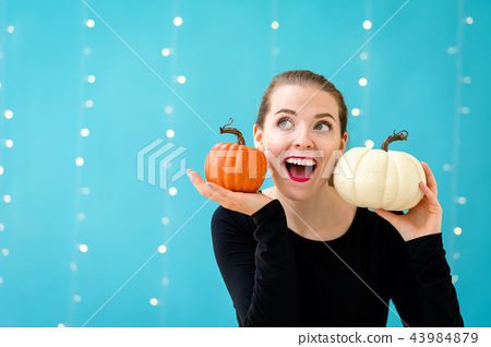Young woman holding pumpkins 43984879