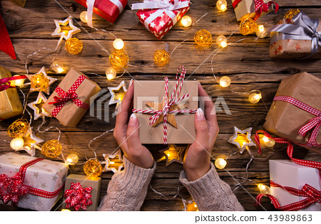 Top view of woman hands with gift box. 43989863