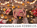 Top view of woman hands with gift box. 43990135