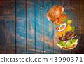 Big tasty burger with flying ingredients. 43990371