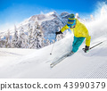 Skier skiing downhill in high mountains 43990379