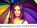 Woman standing under colorful rainbow umbrella 43992059