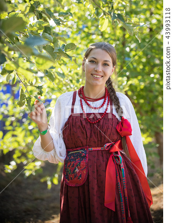 Smiling young woman in russian folk costume on the foliage background 43993118
